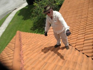 Expert on roof indicating Hurricane Wilma damage to Plaintiffs' home.